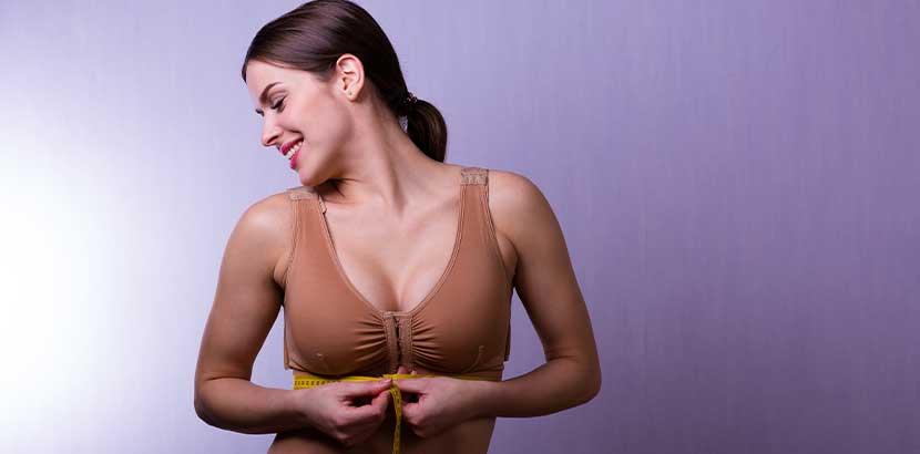 Junge Frau vor lila Hintergrund, die ihren Kompressions BH schließt und lächelt. Brustvergrößerung Wien Kosten.