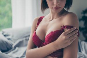 Hübsche Brünette in roten Dessous, die ihren Ausschnitt nach der Brustvergrößerung präsentiert. Brustvergrößerung Wien Kosten.