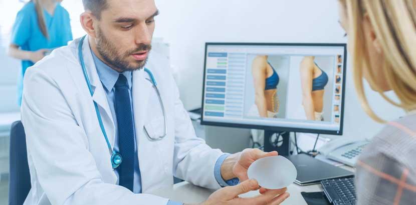 Plastischer Chirurg im Beratungsgespräch mit einer Patientin, die sich eine Brustvergrößerung wünscht.