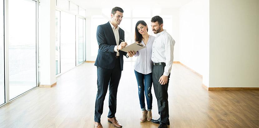 Ein Immobilienmakler, der mit einem Paar eine leere Wohnung begutachtet. Immobilienbewertung