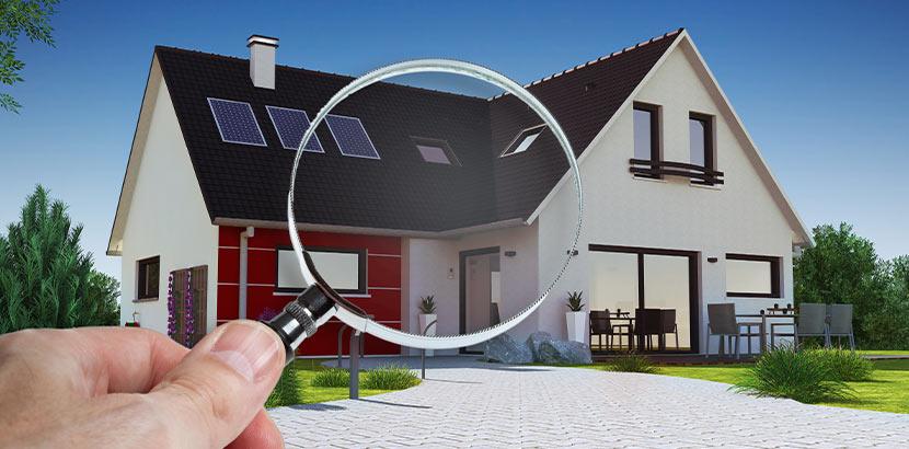 Ein Haus, vor das eine Hand eine Lupe hält. Immobilienbewertung