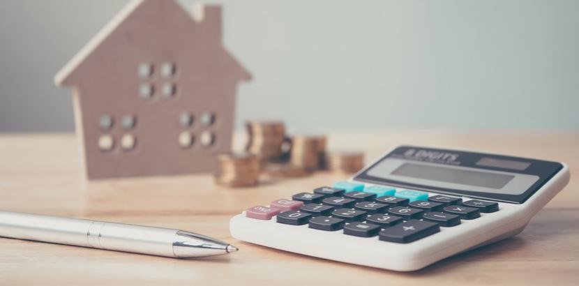 Ein Kugelschreiber und Taschenrechner, die auf einem Tisch vor einem Hausmodell und aufgestapelten Münzen liegen.
