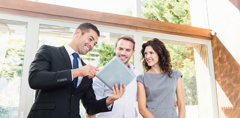 Ein Immobilienmakler, der mit einem Paar auf ein Tablet schaut. Immobilienbewertung.