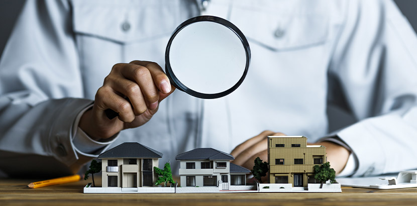Ein Mann mit einer Lupe, der drei kleine Häuser auf einem Tisch untersucht. Immobilienbewertung