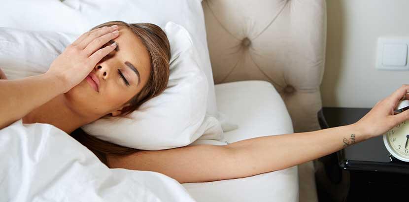 Junge Frau, die am Morgen extrem unausgeschlafen aufwacht und den Wecker ausschaltet. Schlaflabor Wien Kosten.