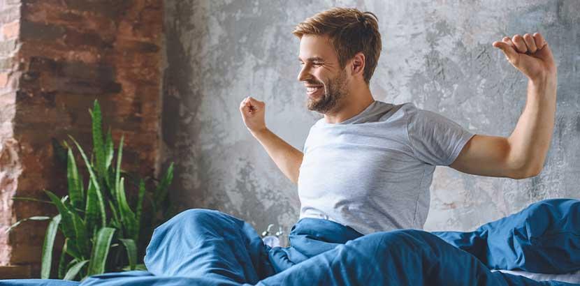 Junger Mann, der im Bett sitzt und sich nach einer erholsamen Nacht lächelnd streckt. Schlaflabor Wien Kosten.