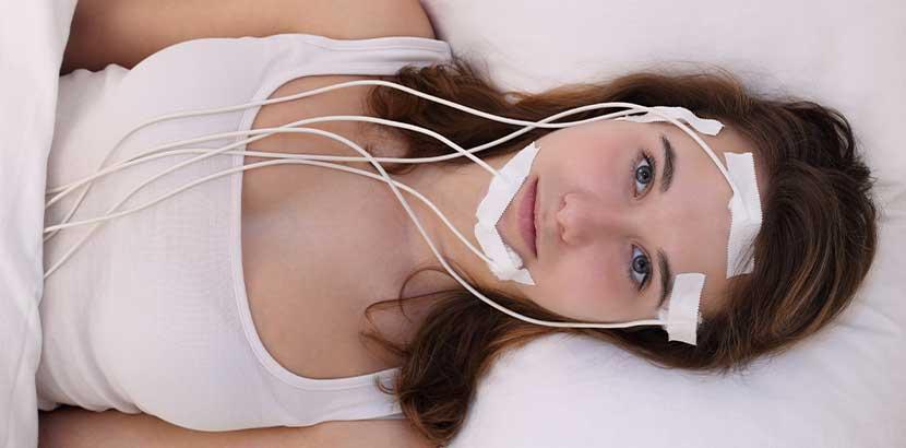 Junge Brünette mit Elektroden am Kopf, die ihre Hirnaktivität messen. Schlaflabor Wien.