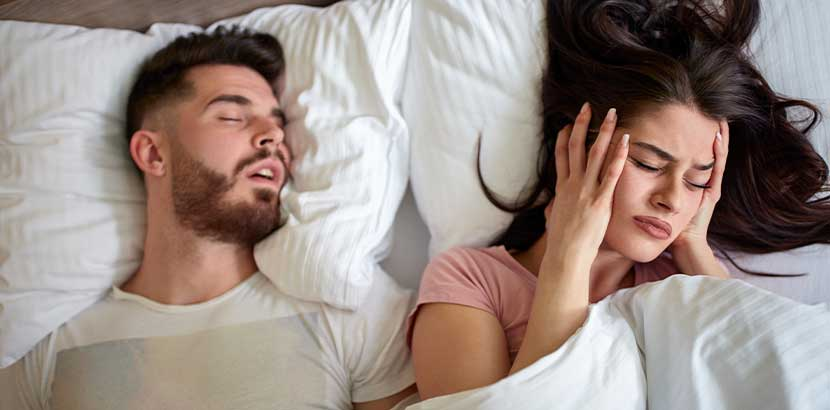 Junge Frau, die mit ihrem Partner im Bett liegt und aufgrund seines Schnarchens nicht schlafen kann. Schlaflabor Wien Kosten.