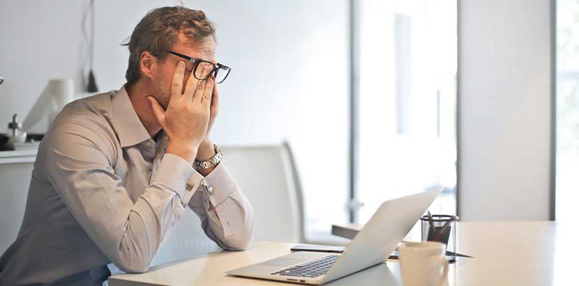 Gestresster Mann, der im Büro am Schreibtisch sitzt und sich müde die Augen reibt. Schlaflabor Wien Kosten.