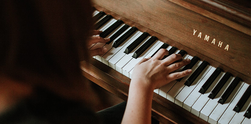 Frau spielt auf Yamaha Klavier
