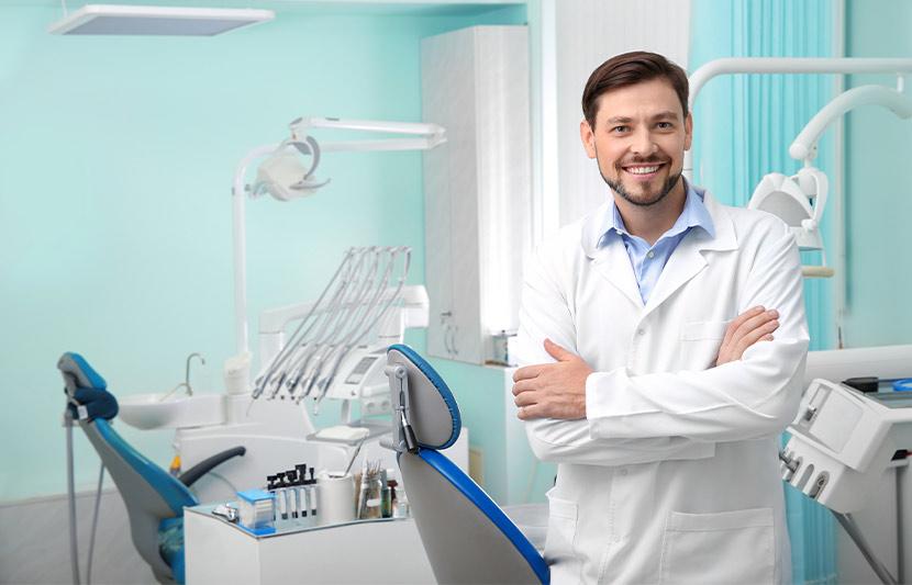 Ein Zahnarzt der mit verschränkten Armen in seinem Behandlungszimmer steht und lächelt. Zahnarzt Graz