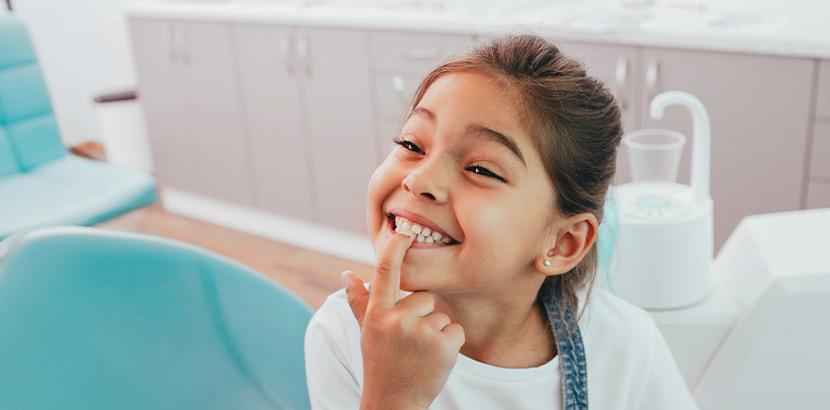 Ein Mädchen auf einem Zahnarztstuhl, das mit dem Finger auf ihre Zähne zeigt.