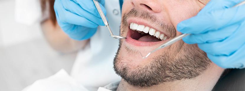 Ein Facharzt für Kieferorthopädie untersucht den Inhalt des Mundes von einem Mann.