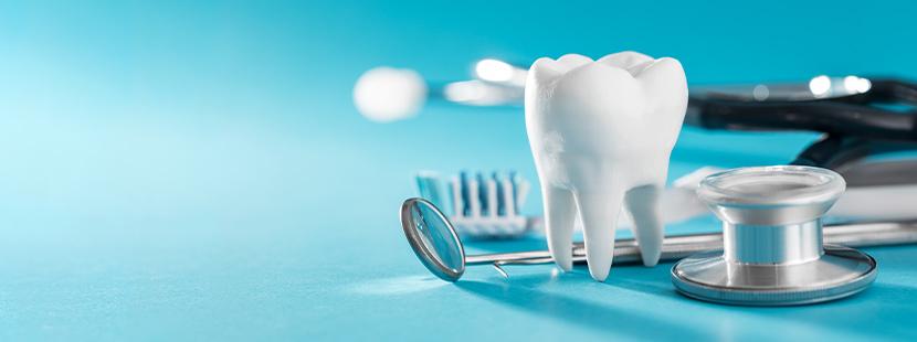 Ein Mundspiegel, eine Zahnbürste und eine Stethoskop, die auf einer blauen Oberfläche liegen.