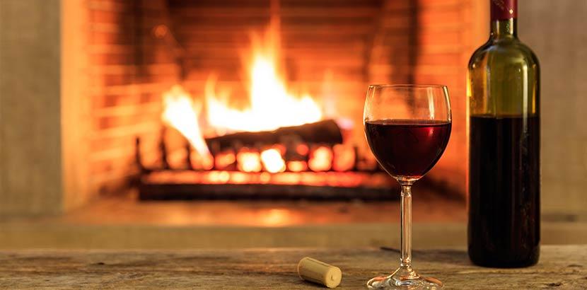 Offener Kamin in einem gemauerten Kamin, vor dem eine Weinflasche und ein gefülltes Rotweinglas auf einem kleinen Tisch stehen.