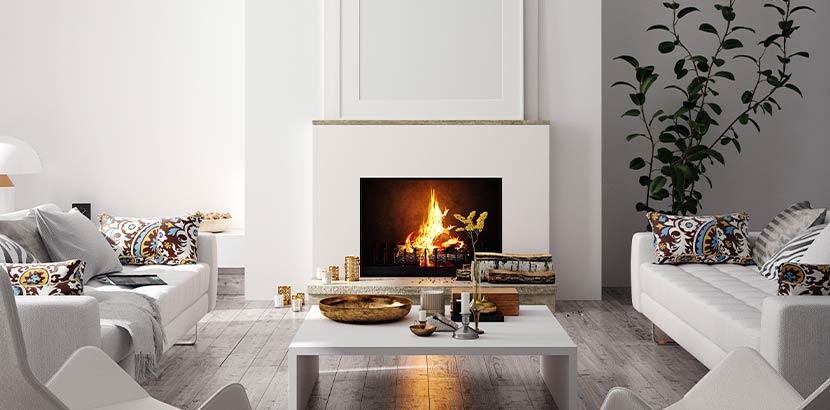 Weiß gemauerter offener Kamin, in dem ein Feuer brennt und der sich harmonisch in ein modern eingerichtetes Wohnzimmer einfügt.