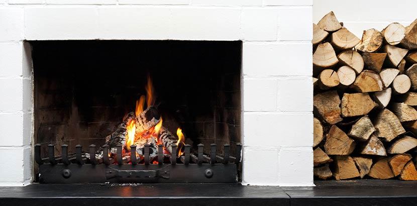 Weiß gemauerter offener Kamin, in dem ein Feuer brennt und neben dem Holzscheite aufgestapelt sind.
