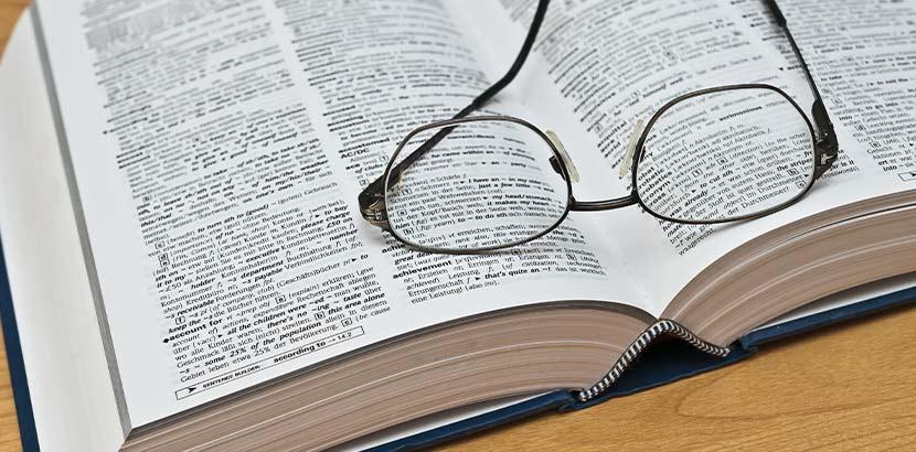 Ein aufgeschlagenes Wörterbuch, auf dem eine Brille liegt.
