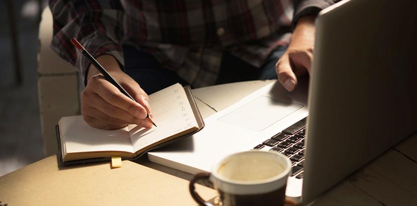 Ein Dolmetscher sitzt mit Laptop und Notizbuch an einem Tisch.