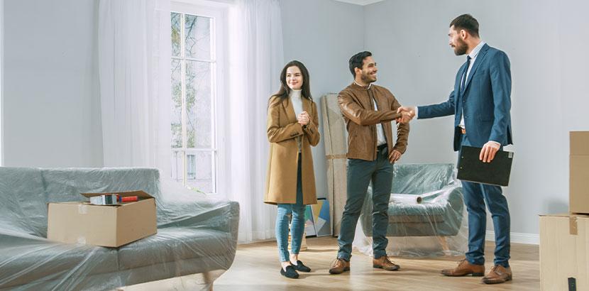 Junges Paar bei einer Wohnungsbesichtigung mit einem Immobilienmakler. Aufgaben Immobilienmakler Wien.