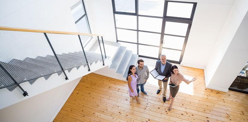 Maklerin und Makler, die einem jungen Paar ein Haus zeigen, das zum Verkauf steht. Aufgaben Immobilienmakler Wien.