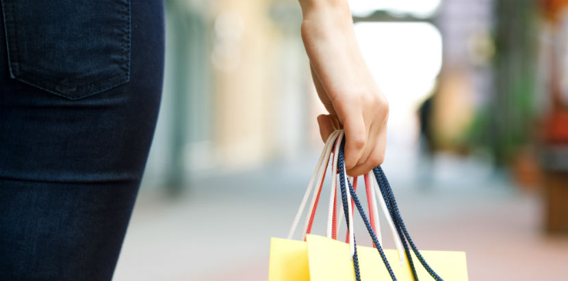 Kaufsucht: eine Frau trägt Einkaufstaschen.