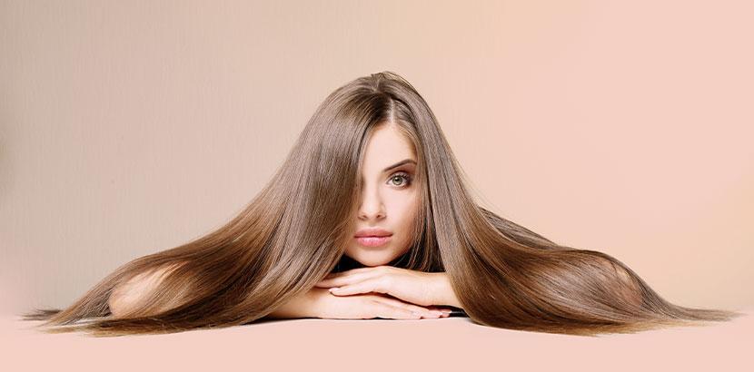 Junge Frau mit langen, glänzenden Haaren nach der Olaplex Behandlung. Olaplex Wien.