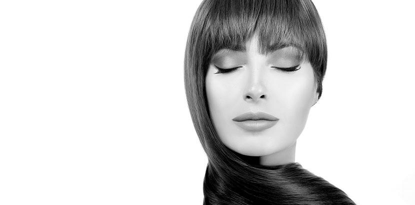 Schwarz-weiß-Aufnahme von einer wunderschönen Frau mit wundervoll durch Olaplex gepflegtem Haar. Olaplex Wien.