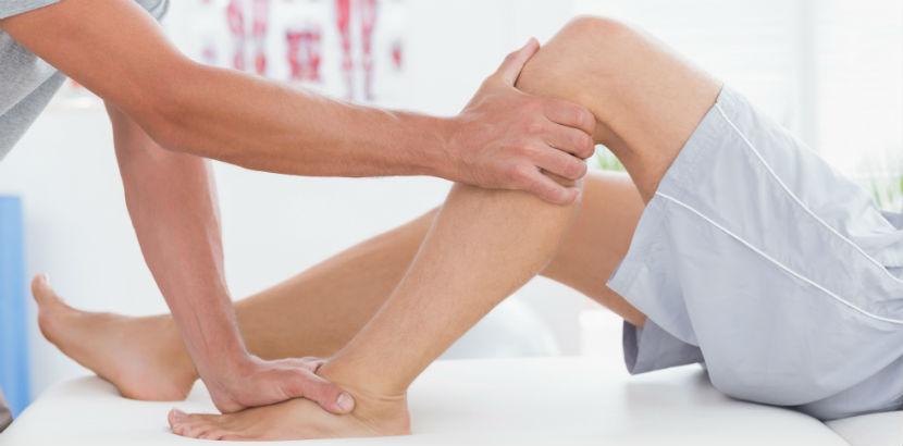 Physiotherapie Graz: ein Therapeut winkelt das linke Bein eines Patienten ab