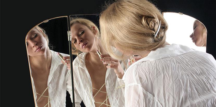 Frau schminkt sich mit Spiegel