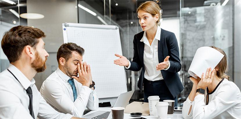 Einige Mitarbeiter streiten in einem Meeting und sind sichtbar gestresst.