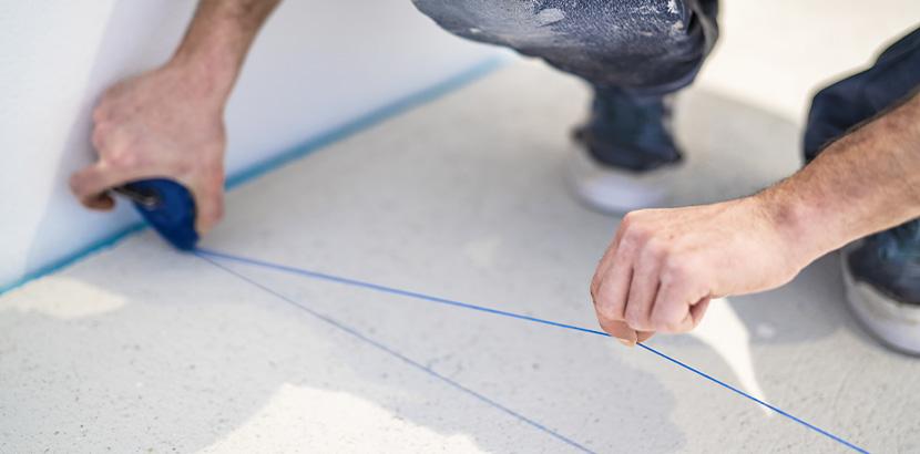 Ein Mann zieht mithlife einer Schlagschnur eine blaue Linie über den Boden.