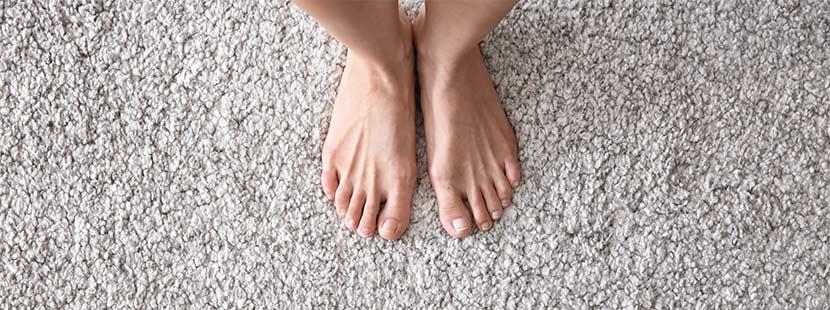 Eine Frau steht barfuß auf Teppichfliesen in Beige