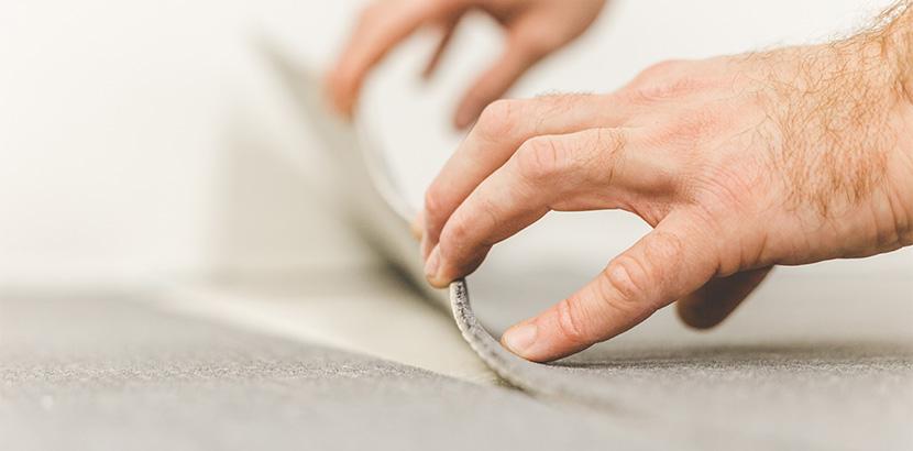 Zwei Hände legen eine Teppichfliese in Position
