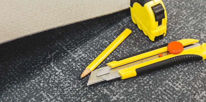 Ein Maßband, ein Bleistift und ein Stanleymesser liegen auf einem Stück Teppich.