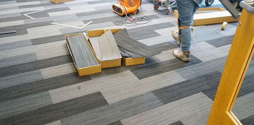 Ein Handwerker verlegt Teppichfliesen in Grau.