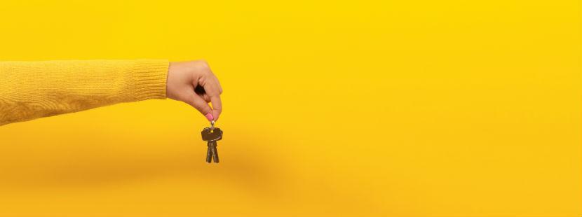 Wohnungssuche: weiblicher Unterarm hält einen Schlüssel in der Hand vor gelbem Hintergrund