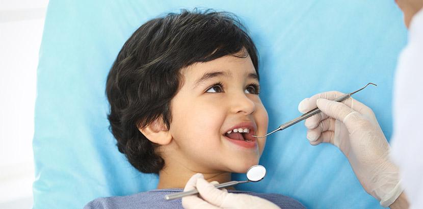 Ein Junge öffnet für den Arzt den Mund und wird mit Sonde und Spiegel untersucht.