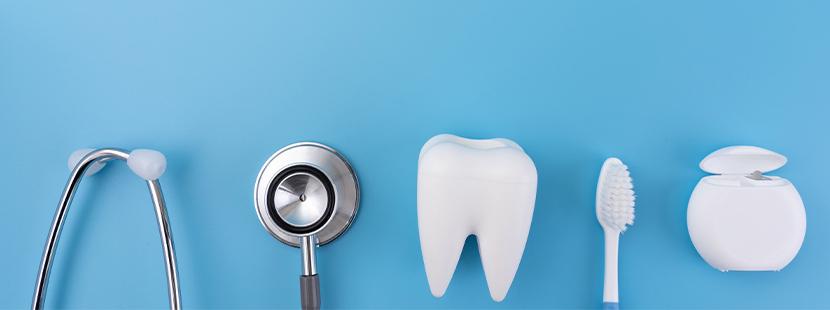 Ein Stethoskop, ein Zahn aus Plastik, eine Zahnbürste und eine Packung Zahnseide liegen auf einem blauen Hintergrund.