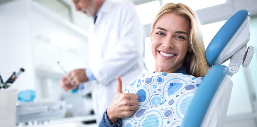 Eine Frau im Zahnarztstuhl lächelt und zeigt Daumen hoch.