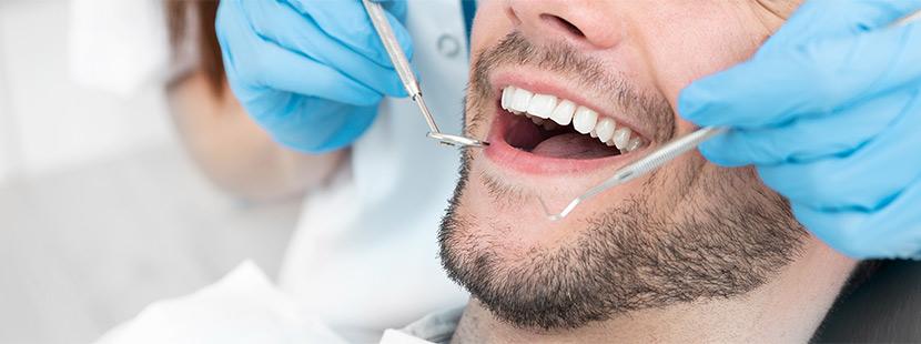 Ein Mann mit geöffnetem Mund lässt seine Zähne untersuchen.