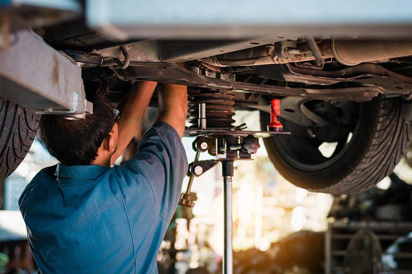 Automechaniker repariert Unterboden eines Autos in einer Autowerkstatt in Salzburg