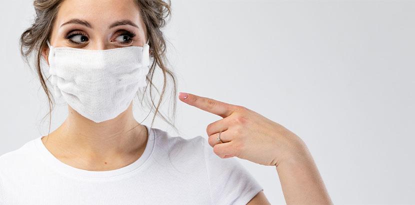 Hübsche junge Frau, die eine Maske zum Schutz vor Corona trägt. Helfen Masken gegen Corona?