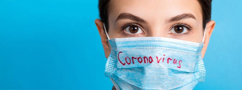 Junge brünette Frau mit einer Mundschutzmaske, auf der Coronavirus geschrieben steht. Corona Maske.