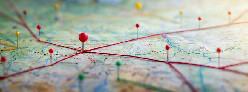 Weltkarte mit unterschiedlich farbigen Pins. Corona Virus aktuelle Lage in Österreich.