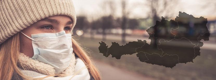 Junge Frau mit Atemschutzmaske, im Hintergrund eine Weltkarte mit Corona-Gebiet.