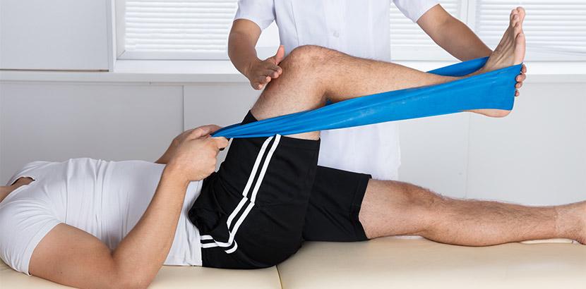 Ein Physiotherapeut dehnt die Muskeln eines betroffenen Patienten.
