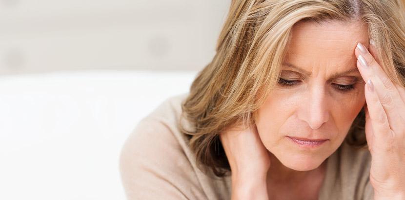 Eine Patientin mit Fibromyalgiesyndrom FMS, die besorgt nach unten blickt.