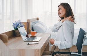 Eine Fibromyalgiepatientin sitzt mit Nackenschmerzen und Rückenschmerzen am Schreibtisch.
