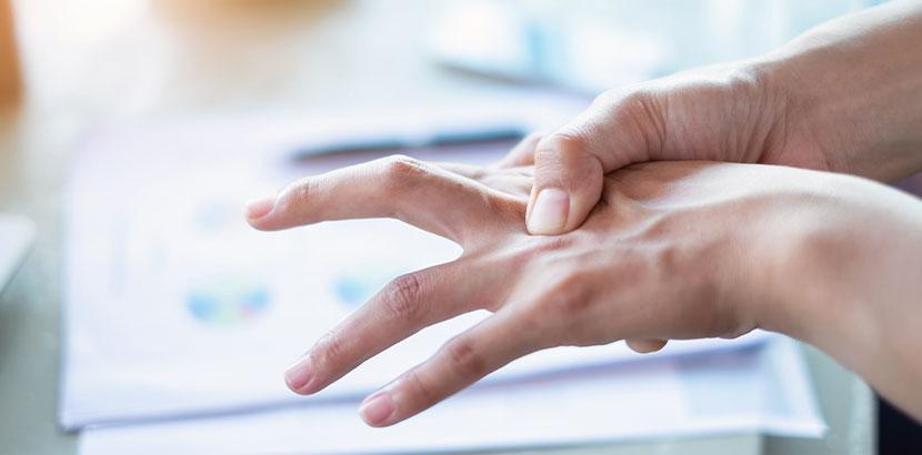 Junge Frau, die sich über der Tastatur die schmerzenden Finger reibt. Handchirurg Wien.